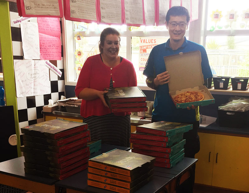 Leo Lee presents the pizza prize to teacher Angela Jones at South Hornby School.