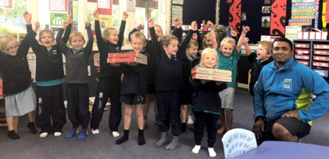 CrestClean business owner Krishna Kumar hands out pizza to children in Willoby Class at Longbeach School in Ashburton.