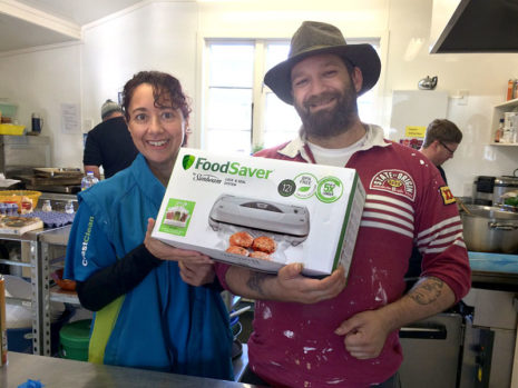 Trish Richards presents a vacuum sealer to Wayne Moss, a team leader at Loaves and Fishes.