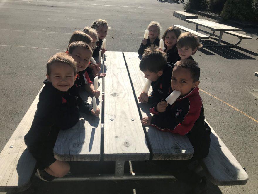 School kids eating ice blocks.