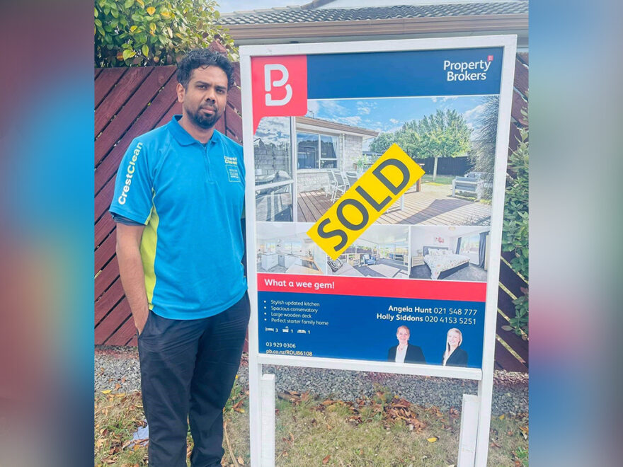 Cleaner standing by real estate sold sign.
