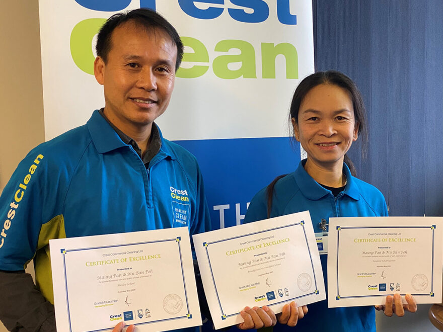 Cleaners proudly holding certificates.