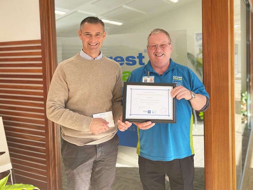 Cleaner being presented with long service certificate.