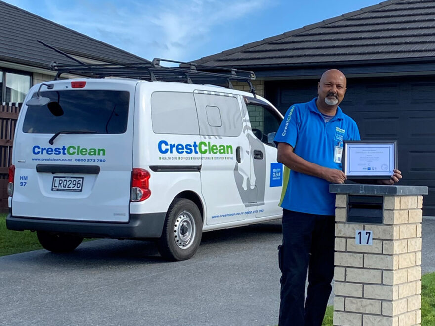 Cleaner standing outside his home with a long service certificate.