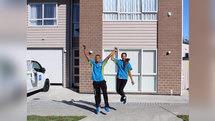 Cleaners jump in the air outside their new home.
