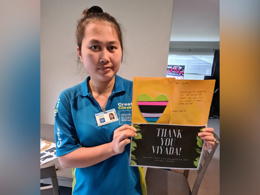 Cleaner holding thank-you card.