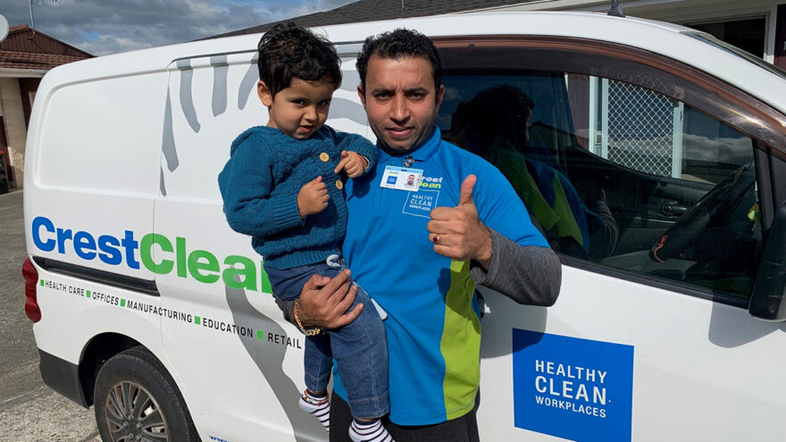 Cleaner holding his son and giving thumbs-up.