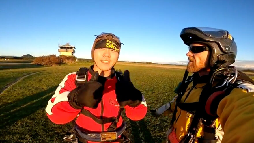Man gives thumbs up after skydive.