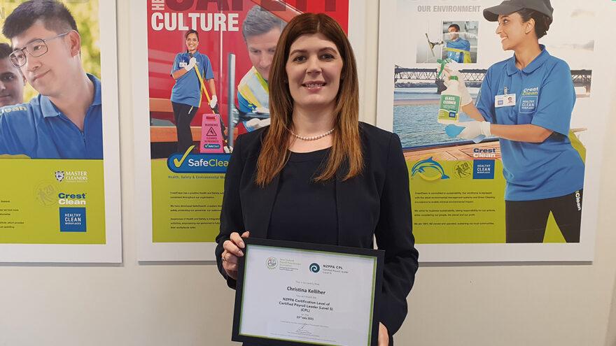 Woman holding framed certificate.