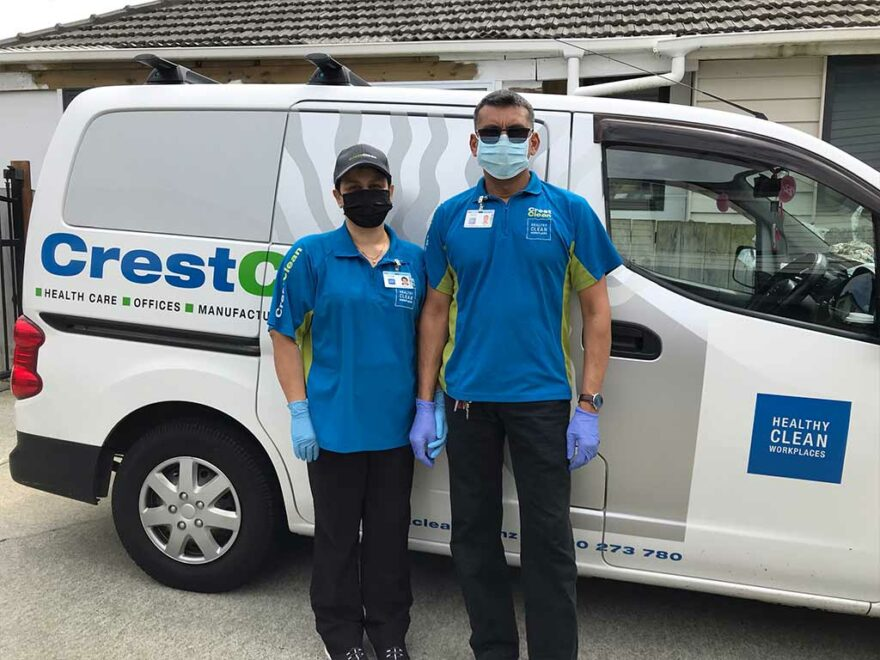 Cleaners wearing masks, standing by their van.